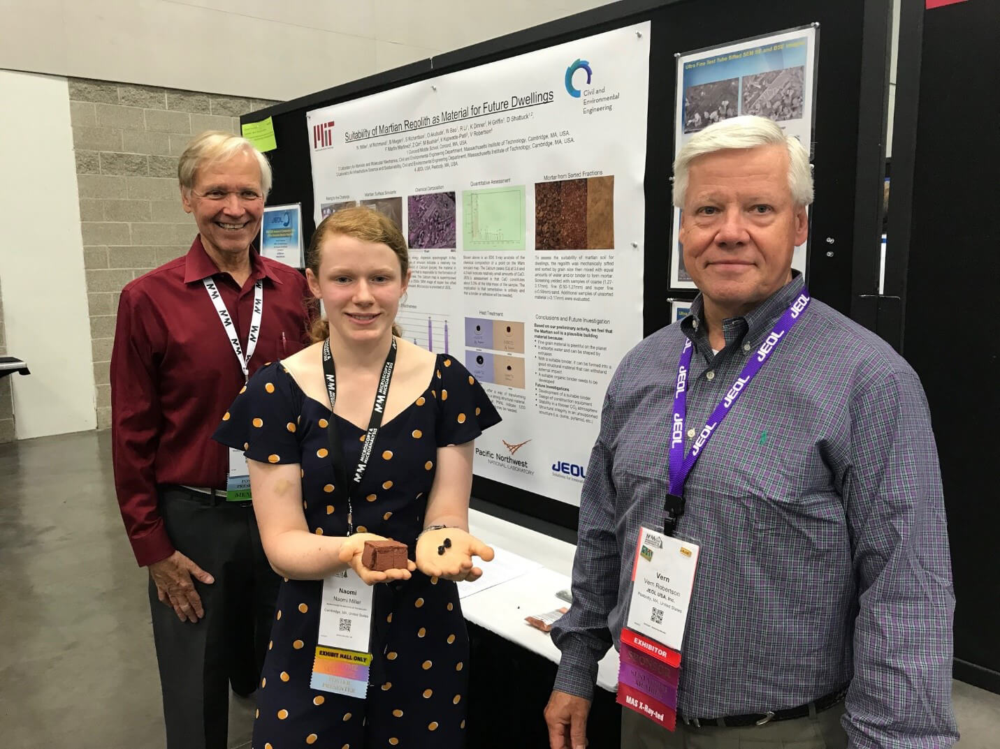 Naomi Miller holds sample of regolith and presented the findings of the CCMS-MIT research group at M&M 2019. Also in photo are her 8th grade teacher, Doug Shattuck (left) and JEOL collaborator Vern Robertson (right).